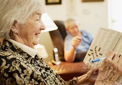 Elderly Couple in Retirement Home, Woman Working on Crossword Puzzle