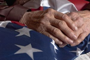 Elderly man's hands resting on the American flag. Lighthouse Senior Living honors Veteran's Day