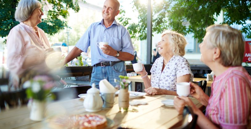 Senior man and women enjoying an outdoor snack and a laugh. Natural light provides a number of benefits from boosting Vitamin D levels to improving mood.