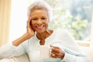 Happy senior woman holding a cup of tea. During a pandemic the necessity of continuing a daily self-care routine can't be overstated.