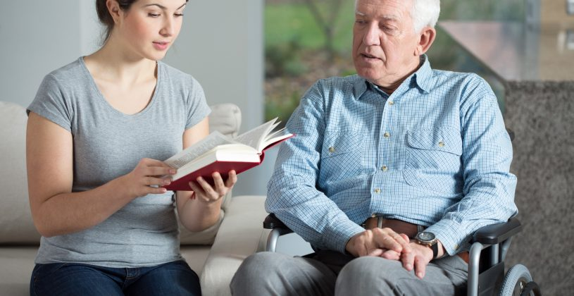 Caregiver reading to a senior with aphasia. Aphasia is a disorder that robs the afflicted of the ability to understand language and communicate normally.