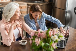 Senior woman and adult daughter at a kitchen table with coffee creating a moving plan on a laptop.