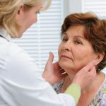 Doctor examines a senior woman's thyroid glands. Thyroid disease impacts around 20 million people in the U.S.