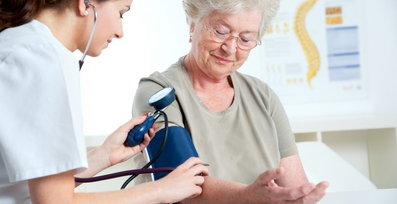 Medical professional checking a senior's blood pressure. Early detection is critical to preventing the most serious effects of hypertension.