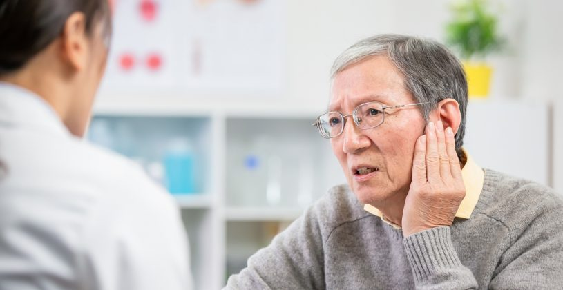 Senior seeing an auditory specialist for assistance with a hearing impairment.