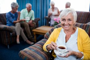 Residents of an assisted living community drinking coffee and socializing in a lounge.