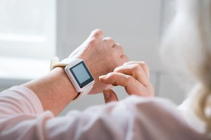 Senior looks at her smartwatch. Wearable technology devices offer several benefits to seniors.