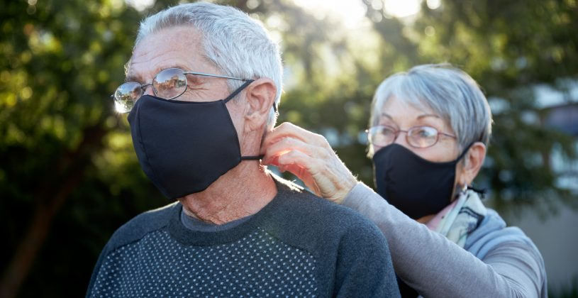 Active senior couple wearing snug fitting masks as a precaution against COVID-19.